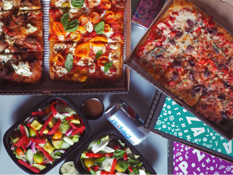 Pizza from P.Za kitchen in boxes with salads and soda on the side.